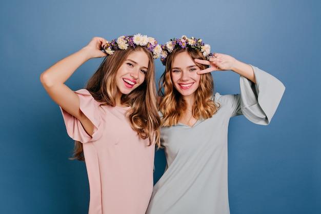 花の花輪で親友と楽しんでいるピンクの服装の魅力的な若い女性 無料写真