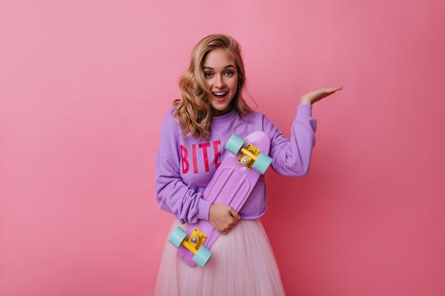 Обаятельная молодая женщина в модной одежде, выражая счастье. восторженная девушка с волнистыми волосами, держащая фиолетовый скейтборд. Бесплатные Фотографии