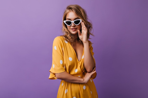 Winsome young woman playfully touching her sunglasses. indoor portrait of happy curly girl isolated on purple. Free Photo