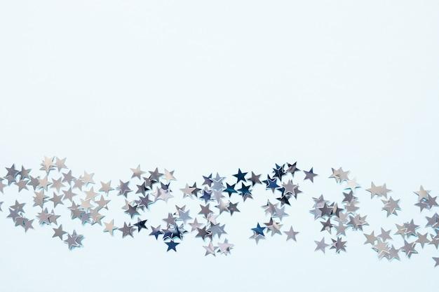 Зимний абстрактный фон с серебряной фольгой конфетти звезд на синем Premium Фотографии