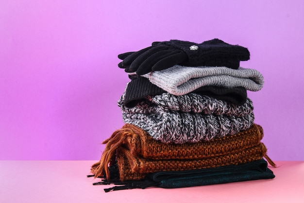 Winter and autumn clothes, hats, scarves, gloves on a purple pastel background. Premium Photo