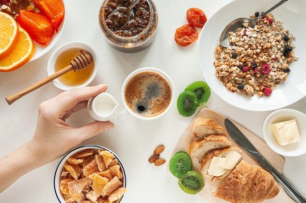 Зимний завтрак с мюсли из сухофруктов и цукатами на белом столе. женская рука держит молочника за чашкой свежего кофе. вид сверху. фото высокого качества Premium Фотографии
