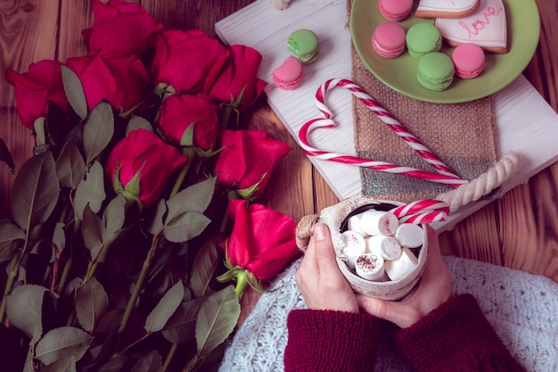 Winter breakfast with red rose and heart of striped lollipop Premium Photo