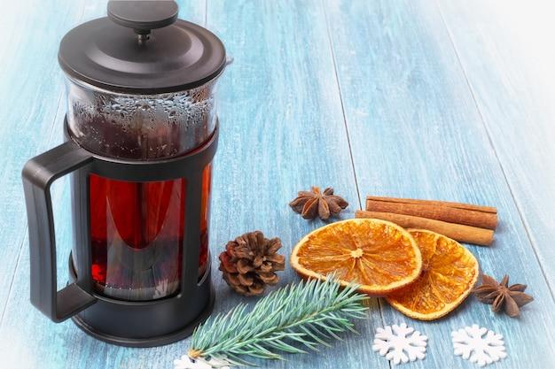冬クリスマスヴィンテージ静物:テクスチャ、青い木製の表面に紅茶、みかん、乾燥オレンジ、シナモンスティック、アニス星とフレンチプレス Premium写真