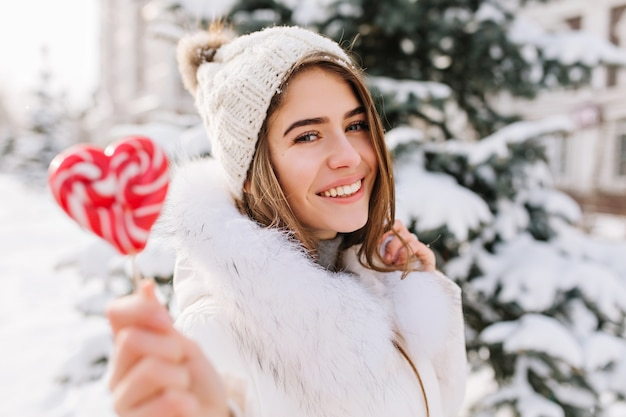 Inverno closeup ritratto affascinante gioiosa giovane donna nella soleggiata mattina d'inverno con lecca-lecca rosa sulla strada Foto Gratuite