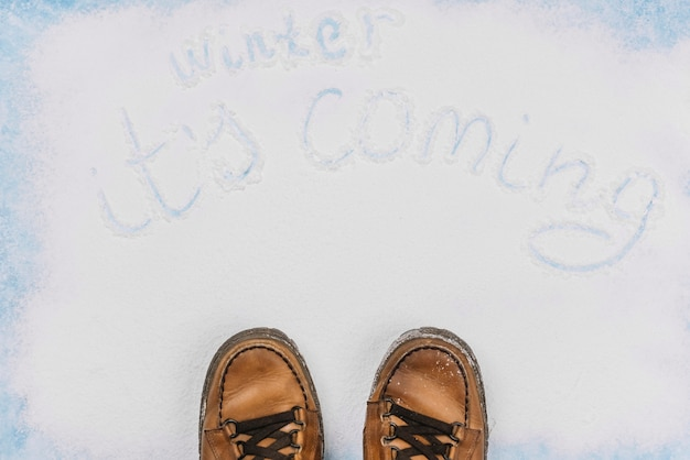 Winter coming writing with brown shoes down Free Photo