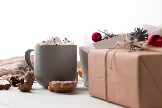 The winter composition. the gifts and cup with marshmallow Free Photo