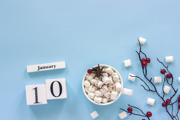 Winter composition. white wooden calendar cubes. data january 10. cup of cocoa, marshmallows and decorative branch Premium Photo