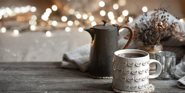 Composizione invernale con una bella tazza di bevanda calda e una teiera su uno sfondo sfocato con bokeh. Foto Gratuite