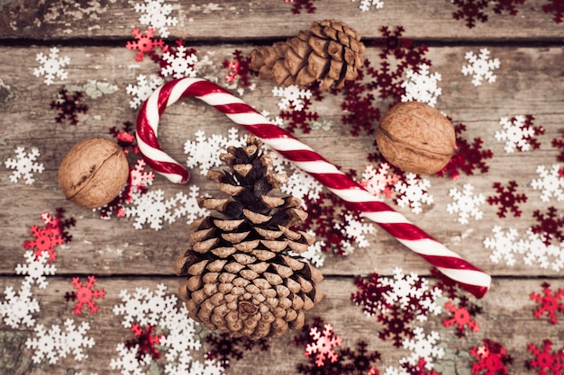 Winter composition with pine cones, walnuts and lollipop Premium Photo
