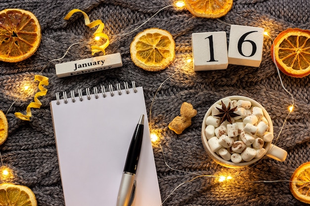 Winter composition. wooden calendar january 16th cup of cocoa with marshmallow, empty open notepad with pen, dried oranges, light garland on grey knitted background. top view flat lay mockup Premium Photo