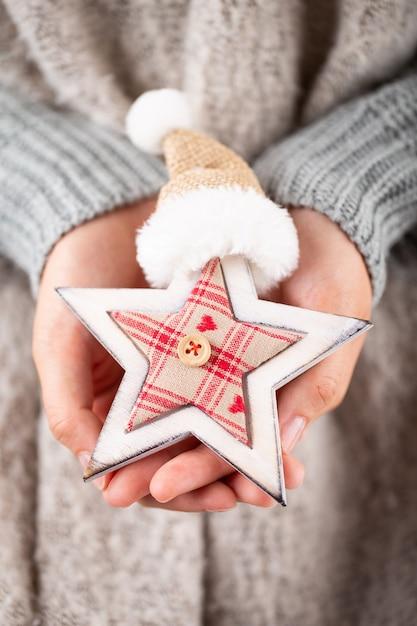 겨울 개념 젊은 손을 잡고 크리스마스 장식. 크리스마스 장식 아이디어. 여자, 골드 Bokeh와 배경의 손에 크리스마스 장식. 프리미엄 사진