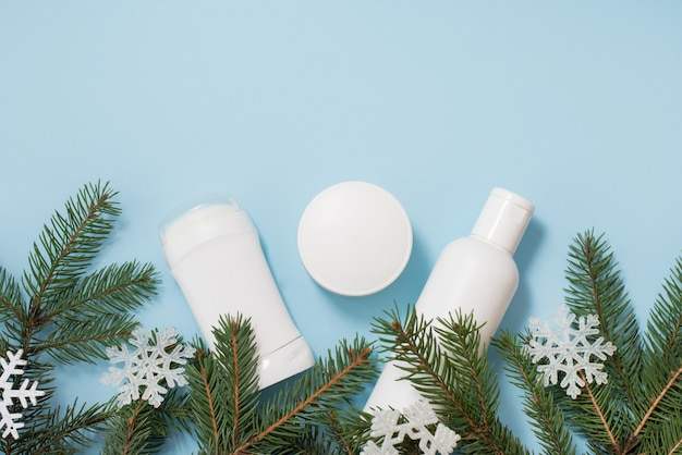 Winter cosmetics antiperspirant, gel and cream with green tree and snowflakes on blue , copyspace.  body care Premium Photo