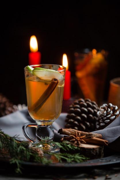 Зимний напиток с палочкой корицы и ломтиком яблока в рождественском столе Бесплатные Фотографии