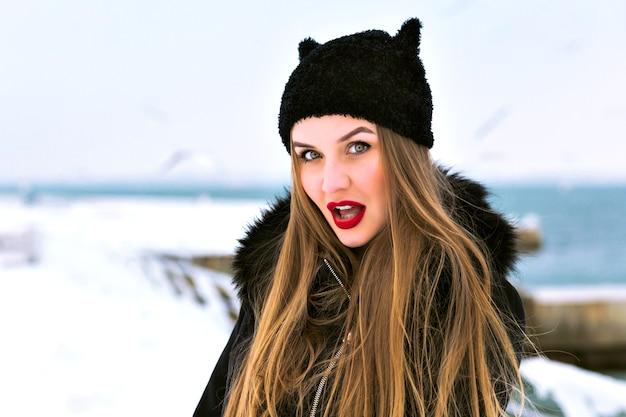 Ritratto di moda invernale di donna bionda sensuale, labbra carnose rosse, molta neve, cappello divertente, cappotto elegante, spedizione di viaggio invernale, capelli lunghi, tempo ventoso, incredibile mare ghiacciato. Foto Gratuite