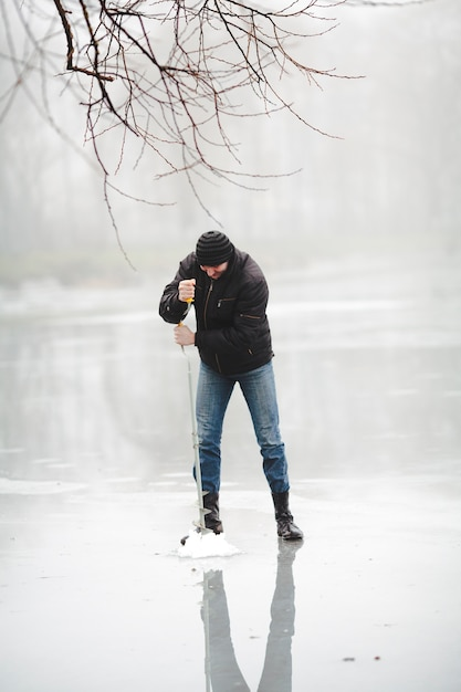Winter fishing on the frozen lake with hand drill Free Photo