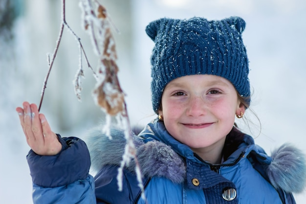 Winter, happy smiling girl holding a frozen branch of a tree_ Premium Photo