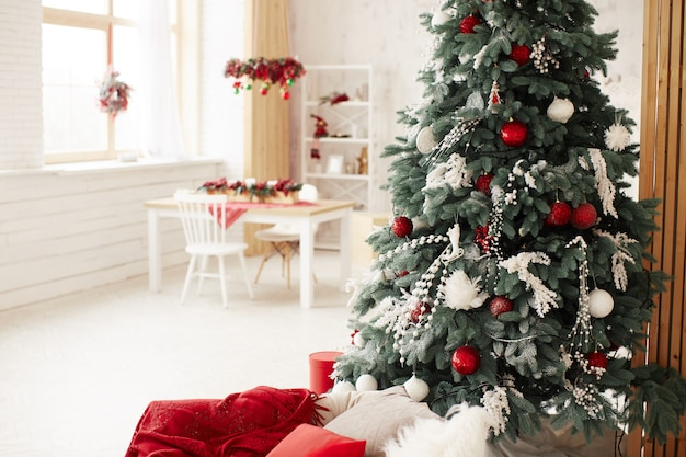 Winter holidays decor. rich decorated new year tree stands with present boxes Free Photo
