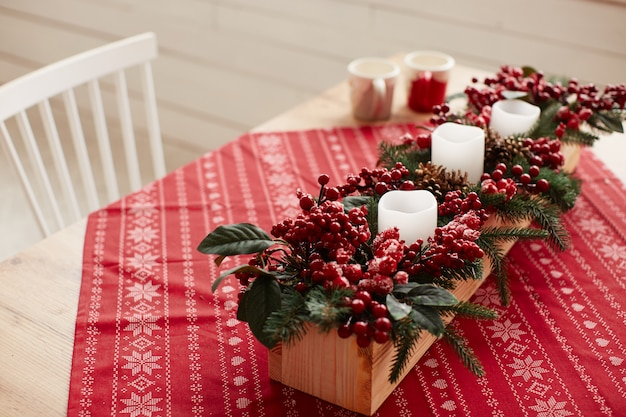 Winter holidays decor. studio preparations. wooden dish with red berries and flowers Free Photo