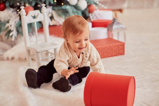 Winter holidays decorations. warm colors. beautiful little girl plays with present boxes Free Photo
