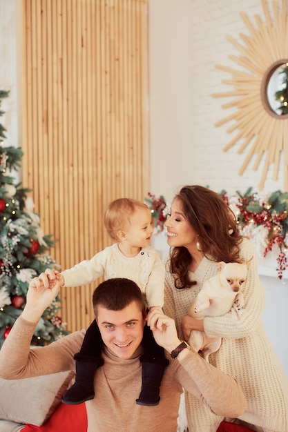 Winter holidays decorations. warm colors. family portrait. mom, dad and their little daughter Free Photo