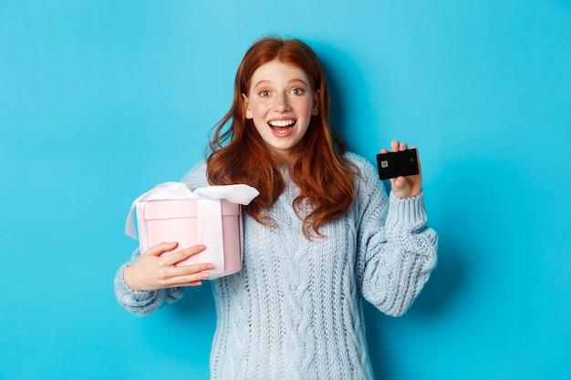 겨울 휴가 프로모션 제공 개념. 쾌활 한 빨간 머리 여자 크리스마스 선물 및 신용 카드를 들고 카메라를 쳐다보고 놀 랐 다, 파란색 배경 위에 서. 프리미엄 사진