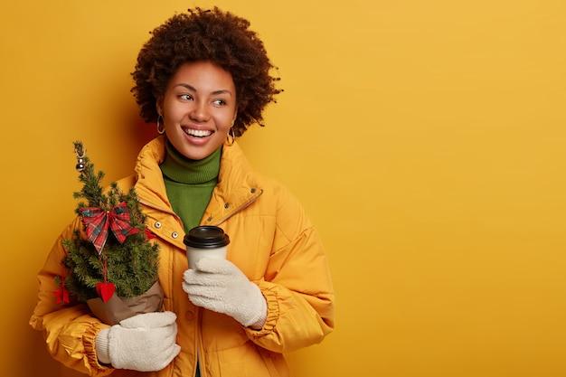 Зима, горячие напитки и люди концепции. счастливая кудрявая женщина пьет кофе на вынос, держит небольшую украшенную елку, готовится к празднованию рождества Бесплатные Фотографии