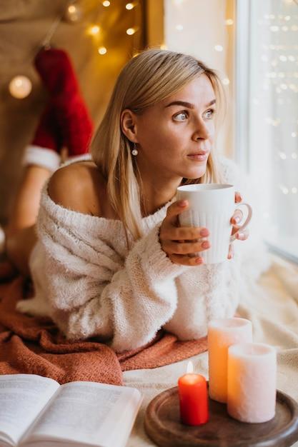 Disposizione hygge invernale con candele accanto alla donna Foto Gratuite