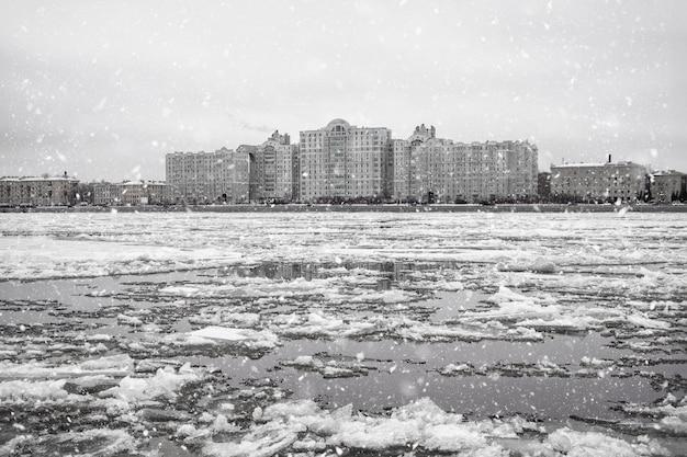 川の冬の氷の漂流。都市の沿岸建築に対する川の氷。 Premium写真