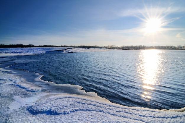 겨울 풍경, 푸른 하늘과 밝은 햇빛, 눈으로 덮인 호수 해안, 나무가 수평선에 자랍니다. 프리미엄 사진