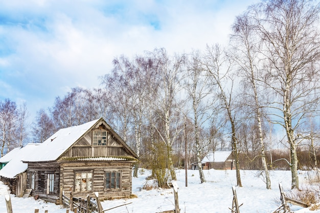 Winter landscape with old wooden house and trees with blue cloudy sky, Premium Photo