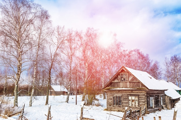 Winter landscape with old wooden house and trees with sunlight and blue cloudy sky. amazing winter scene Premium Photo