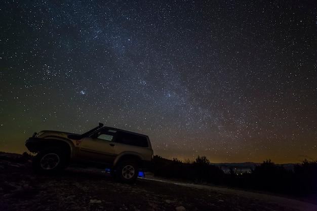 スペイン、レリダ、セラデルモンセックの冬の天の川と4x4車 Premium写真