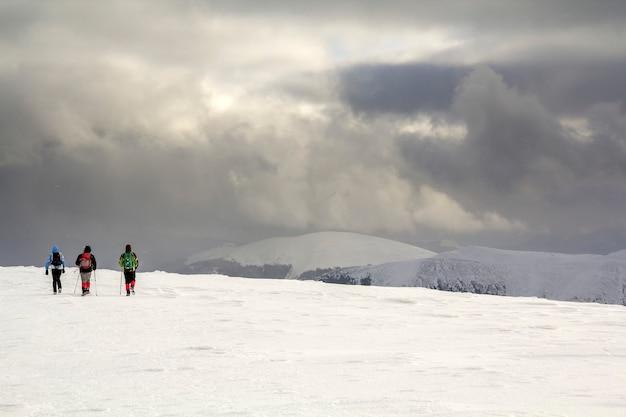 冬の山の風景。曇った紺色の嵐の空のコピースペースの背景にある遠くの山に向かって歩いている雪原にバックパックを背負って明るい服を着た3人の旅行者の観光ハイカー。 Premium写真