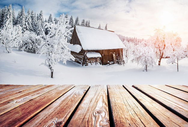 Winter mountains landscape with a snowy forest and a wooden hut and shabby table. Premium Photo