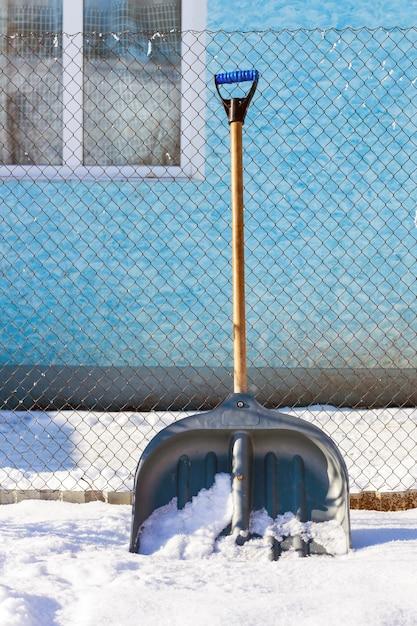 冬、家の近くには雪から領土を掃除するためのシャベルがあります Premium写真