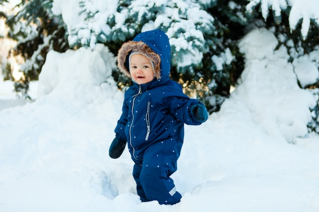Winter, new year and christmas holidays, the child walks on snow in a warm winter overall, Premium Photo