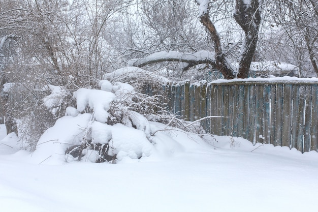 Winter old dilapidated rickety fence of wooden boards. a snow blizzard Premium Photo