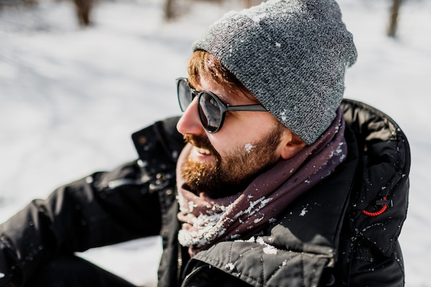 Ritratto di inverno dell'uomo hipster con la barba in cappello grigio rilassante nel parco soleggiato con fiocchi di neve sui vestiti Foto Gratuite