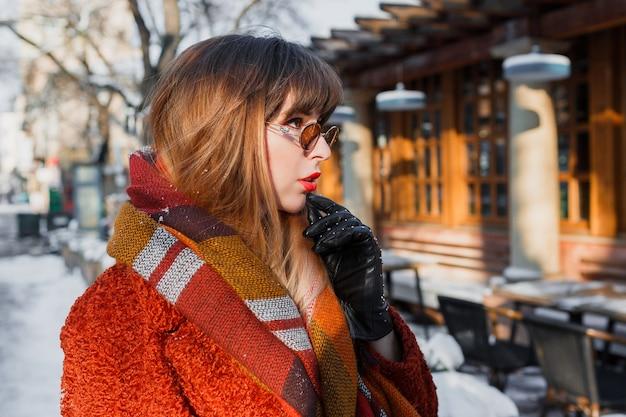屋外ポーズレトロなメガネでエレガントなブルネットの女性の冬のポートレート 無料写真