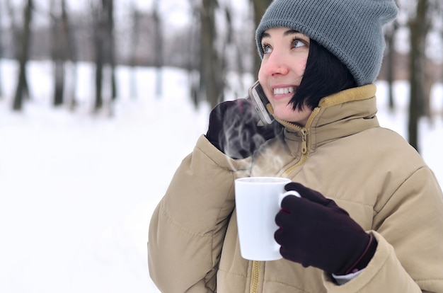 Winter portrait of young girl with smartphone and coffee cup Premium Photo
