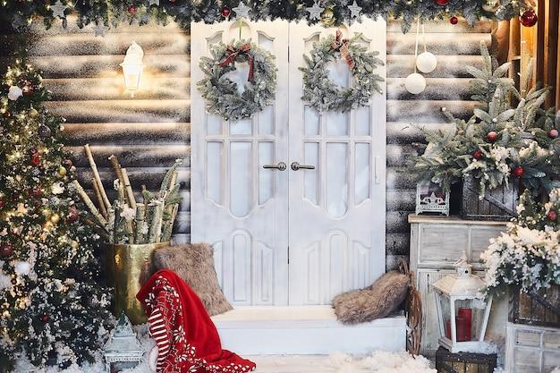 Зимний деревенский интерьер украшен на новый год искусственным снегом и елкой. зимний экстерьер загородного дома с рождественскими украшениями в деревенском стиле. Premium Фотографии