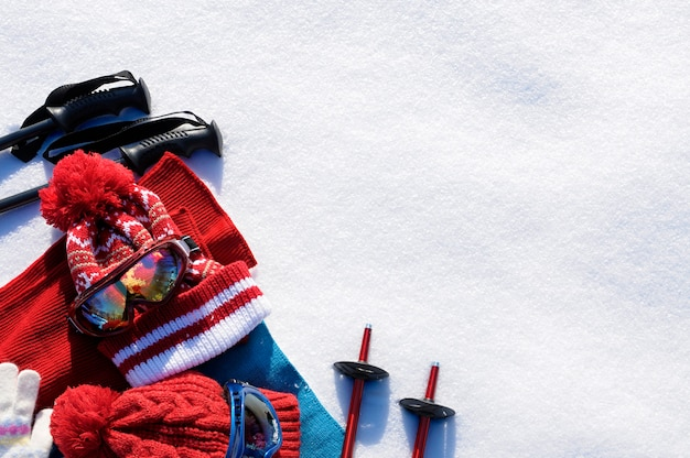 Winter snow sports background with ski poles, goggles, hats and gloves with copyspace. Free Photo
