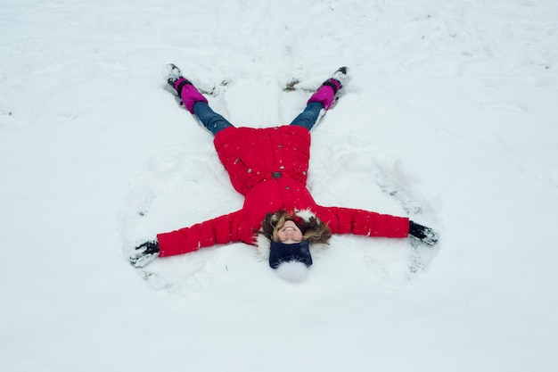 Winter time,cheerful girl having fun in the snow, top view Premium Photo