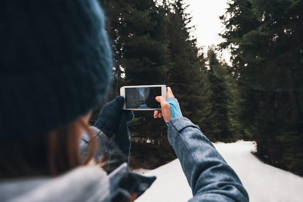 Концепция зимнего путешествия - женщина вид сзади, снимающая зимний лес на смартфон Premium Фотографии