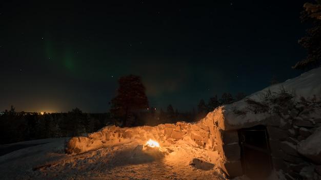 어두운 밤 하늘, 핀란드에서 오두막과 오로라 근처 화재의 겨울보기 프리미엄 사진