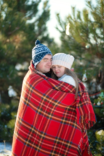 Winter walk through the woods, the guy in the red plaid blanket wraps the girl up so she gets warm Premium Photo