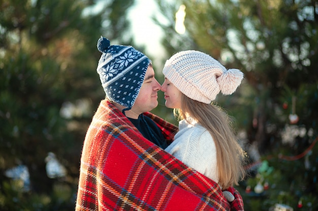 Winter walk through the woods. the guy with the girl kissed wrapped in a red checkered plaid Premium Photo