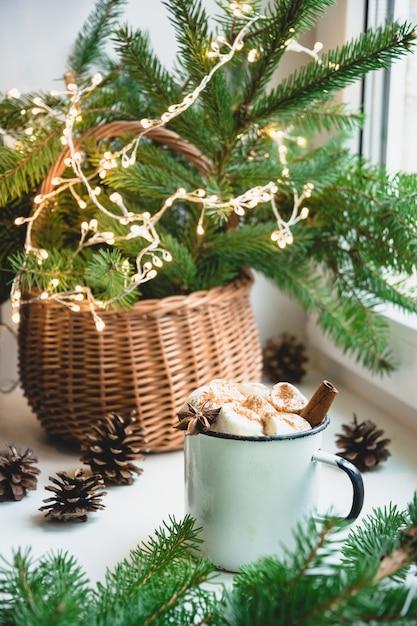 Winter warming mug of chocolate with marshmallow on windowsill. Premium Photo