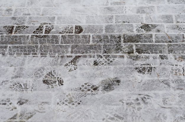 Wintertime - road covered with snow with traces of car tires and shoe prints Premium Photo